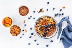 De havermoutpap van het chocoladehavermeel met bosbes, noten, banaan, droge abrikoos voor gezonde ontbijt Hoogste mening royalty-vrije stock fotografie
