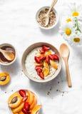 De havermoutpap van het kokosmelkhavermeel met aardbeien, abrikozen, honing en lijnzaad Heerlijk gezond ontbijt op een lichte ach stock afbeeldingen