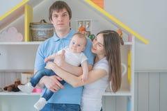De hechte familie van Nice van mamma, papa en dochter het stellen in hun witte ruimte stock afbeelding