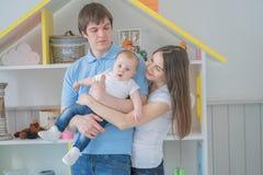 De hechte familie van Nice van mamma, papa en dochter het stellen in hun witte ruimte stock foto's