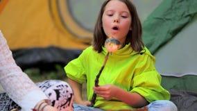 De heemst van het meisjesbraadstuk over een kampvuur stock footage