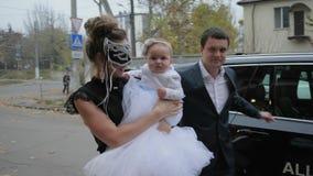 De heer helpt vrouw in Venetiaans masker met baby om uit auto voor een avondgebeurtenis te krijgen stock videobeelden