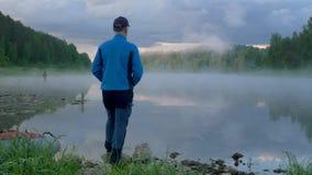De heer neemt en geniet van dageraad op duidelijke meerbank waar stock footage