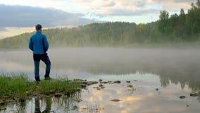 De heer neemt en geniet van dageraad op duidelijke meerbank waar stock videobeelden