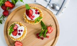 De heerlijke Belgische wafels met wipped room en aardbeien op ronde houten plaat stock afbeeldingen