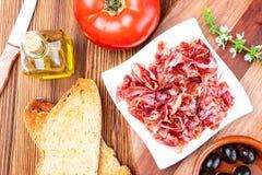 De heerlijke broodtoost met natuurlijke tomaat, extra eerste persing, Iberische ham, zwart olijven en basilicum gaat weg royalty-vrije stock afbeeldingen