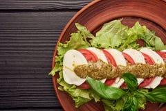 De heerlijke caprese salade met rijpe tomaten en mozarellakaas met vers basilicum gaat weg Italiaans voedsel royalty-vrije stock afbeelding