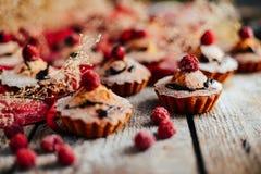 De heerlijke chocolade cupcakes met bessen wodeen lijst, bovenkant v Stock Afbeeldingen
