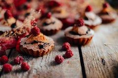 De heerlijke chocolade cupcakes met bessen wodeen lijst, bovenkant v Stock Foto's