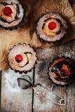 De heerlijke chocolade cupcakes met bessen wodeen lijst, bovenkant v Royalty-vrije Stock Afbeelding
