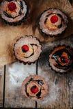 De heerlijke chocolade cupcakes met bessen wodeen lijst, bovenkant v Stock Foto