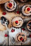 De heerlijke chocolade cupcakes met bessen wodeen lijst, bovenkant v Royalty-vrije Stock Foto's