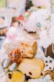 De heerlijke die samenstelling van de kaas, brood en de paddestoelen door bloemen in de houten potten wordt het omringd Royalty-vrije Stock Fotografie