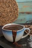 De heerlijke gesmolten chocoladesaus in mok met zwaait op lijst Royalty-vrije Stock Afbeeldingen