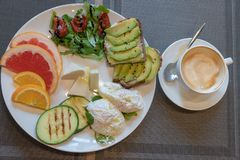 De heerlijke gezonde ontbijttoosts met avacado, droge tomaten, kaas, apelsin, grapefruit, stroopten ei, courgette op de grill royalty-vrije stock fotografie