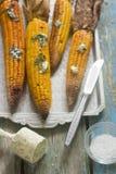 De heerlijke gouden geroosterde maïskolven dienden in openlucht met een krul van verse boerenboter stock afbeeldingen