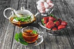 De heerlijke groene thee van de muntaardbei in een transparante glastheepot en Kop in de zomer, op een rustieke houten lijst met  Stock Afbeelding