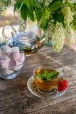 De heerlijke groene thee van de muntaardbei in een transparante glastheepot en Kop in de zomer, op een rustieke houten lijst met  Royalty-vrije Stock Afbeelding