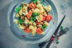 De heerlijke plantaardige tomaten van schotelbloemkool gebakken kekers stock afbeeldingen