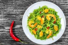 De heerlijke salade van garnalen, mosselen, zeewier, Spaanse pepers en sesam kruidde met extra eerste persing op de witte schotel stock foto