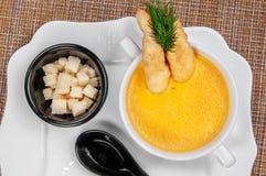 De heerlijke smakelijke garnalensoep met gebraden brood in een kom diende op de lijst en de zwarte lepel Close-up van hierboven royalty-vrije stock foto