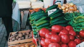 De heerlijke verse komkommerstomaten en andere groenten met prijskaartjes liggen op marktteller stock video