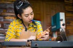 De heerser en het potlood van de vrouwenholding terwijl het maken van tot tekens op het hout de lijst in de workshop royalty-vrije stock afbeeldingen