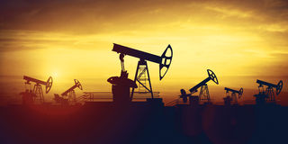 De hefbomen van de oliepomp op de achtergrond van de zonsonderganghemel Stock Foto's