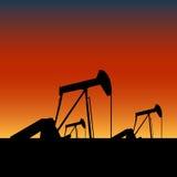 De hefbomen van de pomp op oliebronnen bij zonsondergang Stock Afbeelding