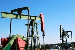 De hefbomen van oliepompen onder blauwe hemel stock foto's