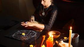 De heks is een fortuinteller met kaarsenclose-up Een magisch ritueel divination Halloween, slow-motion 4k, stock videobeelden