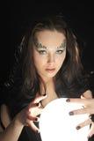 De heks maakt het dit wensen met een Magische kristallen bol Stock Foto's