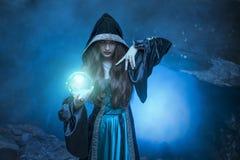 De heks met magische bal in haar handen veroorzaakt geesten royalty-vrije stock foto