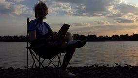 De heldere Blogger-Mens zit op een Vouwende Stoel en bekijkt Zijn Tablet stock videobeelden