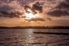 De heldere dramatische zonsonderganghemel met zonstraal glanst van wolk, silhou royalty-vrije stock foto