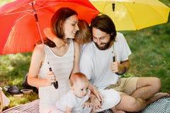 De heldere grote paraplu's omvatten gelukkige familie die gekleed in de witte kleren op de deken van de zon zitten stock foto