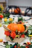 De heldere de herfstregeling van bloemen en bessen in de pompoen stock foto