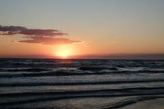 De heldere kleuren van de hemel tegen het donkere water Royalty-vrije Stock Foto's