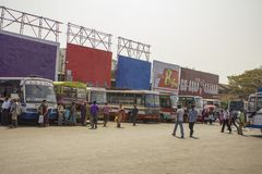 De heldere kleurrijke Indische bussen zijn op een rij in het parkeren bij het busstation en de lopende mensen stock foto