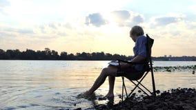 De heldere Mens gaat zitten en schrijft in Zijn Blocnote op Nice Riverbank stock videobeelden