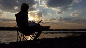 De heldere Mens zit als Voorzitter op Riverbank, leest, en Dranken bij Zonsondergang stock videobeelden