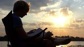 De heldere Mens zit, leest en schrijft Zijn Nota's over een Riverbank bij Zonsondergang stock footage