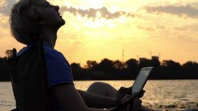 De heldere Mens zit op een Vouwende Stoel en bekijkt Zijn Tabletpc Zonsondergang stock video