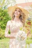 De heldere mooie jonge gelukkige vrouw loopt door het park dichtbij een bloeiende boom op een zonnige dag in de zomerhoed en sund Stock Foto's