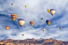 De heldere multi-colored hete luchtballons die binnen sunsrise hemel vliegen Stock Afbeelding
