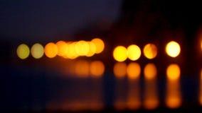 De heldere nachtlichten worden weerspiegeld in zeewater tegen de achtergrond van gebouwen met meerdere verdiepingen Bokeh stock video