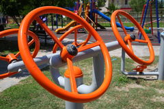 De heldere oranje simulators van metaalstuurwielen op de speelplaats Royalty-vrije Stock Afbeeldingen