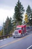 De heldere rode semi klassieke stijl van de vrachtwagen grote installatie op regenweg Royalty-vrije Stock Afbeeldingen