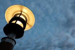 De heldere straatlantaarn is geel op de achtergrond van de avond of ochtendhemel met wolken Royalty-vrije Stock Foto's
