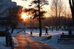 De heldere zon piept uit van achter het gebouw in de winter de sneeuw is op het spoor en de mensen slepen aan het werk en op zake royalty-vrije stock fotografie